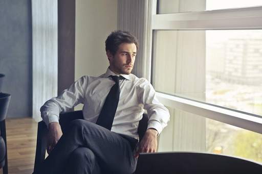 Mężczyzna siedzi na fotelu i patrzy w okno