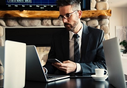 Mężczyzna z telefonem w ręku patrzy w laptop